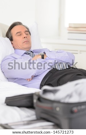 Tired of traveling. Tired mature businessman sleeping on the sofa at home - stock photo