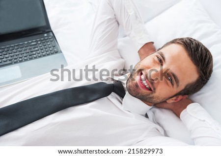 Tired of work. Top view of handsome young man in shirt and tie holding hands behind head and keeping eyes closed while lying in bed at the hotel room  - stock photo
