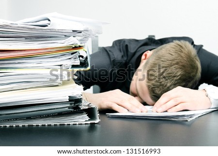 tired office worker and a pile of documents - stock photo