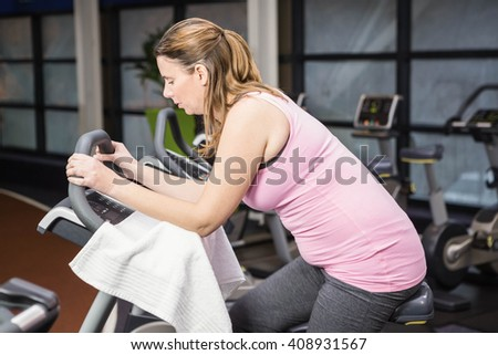 Tired pregnant woman on exercise bike at the gym - stock photo