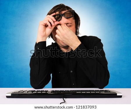 Tired programmer with headache - stock photo