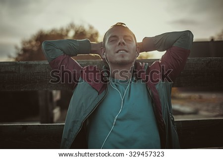tired runner sitting, relaxing and listening to music on your phone, eyes closed on a wooden pier, sport. - stock photo