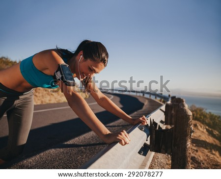Tired runner taking a break leaning on country road guardrail. Fit young woman athlete training outdoors. - stock photo