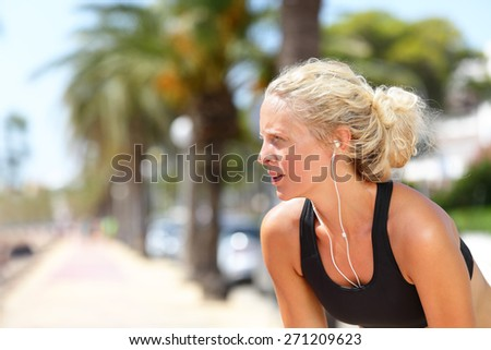 Tired running woman taking a break during run. Beautiful young blond athletic female adult resting catching her breath while jogging and listening to music with earphones and smartphone app. - stock photo