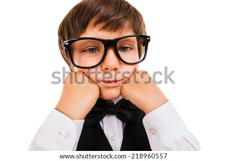 Tired schoolboy. Bored little boy leaning his face on hands and looking at camera while isolated on white - stock photo