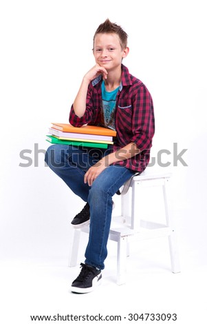 tired schoolboy European appearance in shirt and jeans sitting on a chair with a book. Photo from the depth of field - stock photo