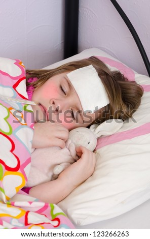 Tired sick little girl sleeping in bed - stock photo
