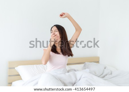 Tired sleepy woman waking up and giving a stretch - stock photo