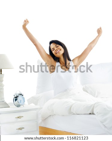 Tired sleepy woman waking up and yawning with a stretch while sitting in bed isolated on white background - stock photo