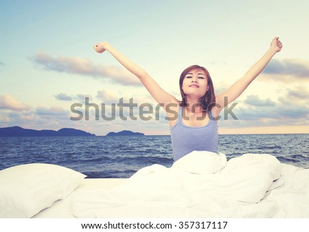 Tired sleepy woman waking up and yawning with a stretch while sitting in bed, sea view - stock photo