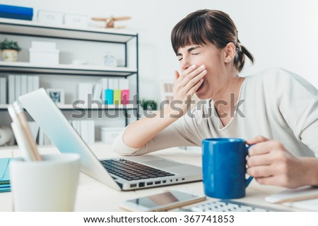 Tired sleepy woman yawning, working at office desk and holding a cup of coffee, overwork and sleep deprivation concept - stock photo