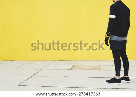 Tired sportsman after intensive jog athletic runner resting on yellow wall background at sunny day, attractive sporty man taking break after evening run, fitness and healthy lifestyle concept. - stock photo