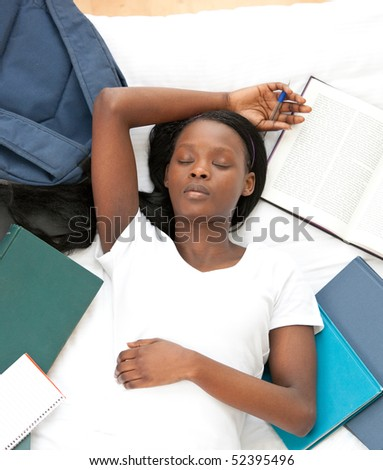 Tired student doing her homework lying on a bed at home - stock photo
