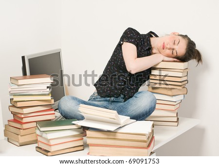 Tired student girl have slept on desk with books and laptop - stock photo
