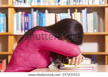 Tired student girl sleeping on the table at the library - stock photo