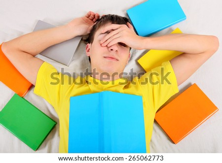 Tired Teenager sleep with a Books on the Bed - stock photo