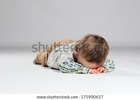 Tired toddler boy lying on the ground with his face down - stock photo