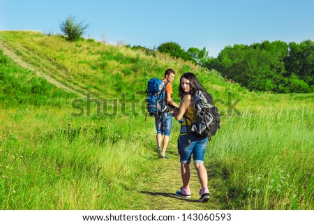 Tired tourists with backpacks hiking - stock photo