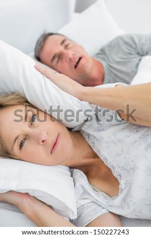 Tired wife blocking her ears from noise of husband snoring looking at camera in bedroom at home - stock photo