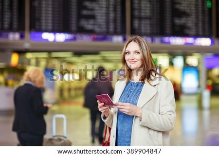Tired woman at international airport walking through terminal. Upset business passenger waiting. Canceled flight due to pilot strike. New York airport, USA - stock photo