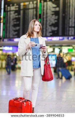 Tired woman at international airport walking through terminal. Upset business passenger waiting. Canceled flight due to pilot strike. Berlin, Germany. - stock photo