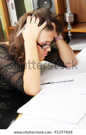 Tired woman behind the desk in the office - stock photo