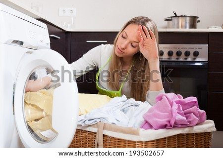 tired woman doing laundry with washing machine - stock photo
