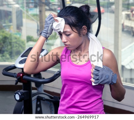 tired woman drying his sweaty forehead with a towel in the gym - stock photo