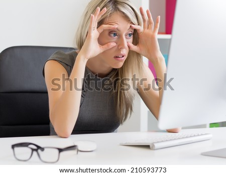 Tired woman in front of computer - stock photo