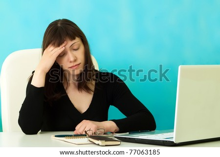Tired woman in office on a blue background - stock photo
