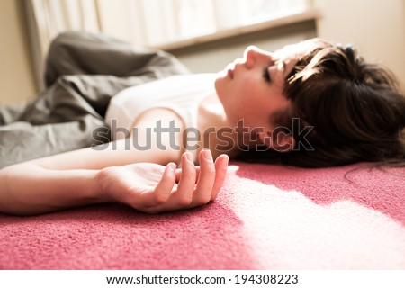 Tired woman laying in bed, relaxing in a close up shot - stock photo