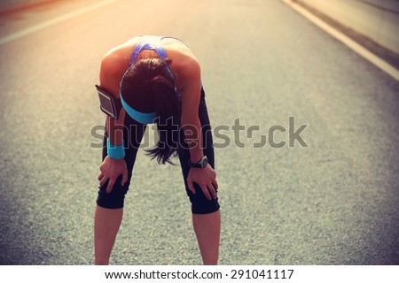 tired woman runner taking a rest after running hard on city road - stock photo