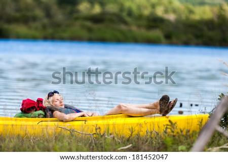 Tired Woman Sleeping in a Yellow Kayak - stock photo