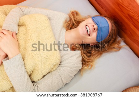 Tired woman sleeping in bed under blanket wearing blindfold sleep mask. Young girl taking nap. - stock photo
