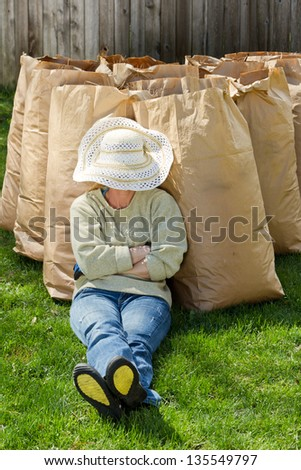 tired woman taking a brake after cleaning up the back yard - stock photo