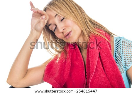 Tired woman wiping sweat off forehead after workout - stock photo