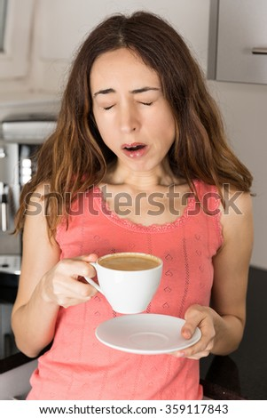 Tired woman with a cup of coffee - stock photo