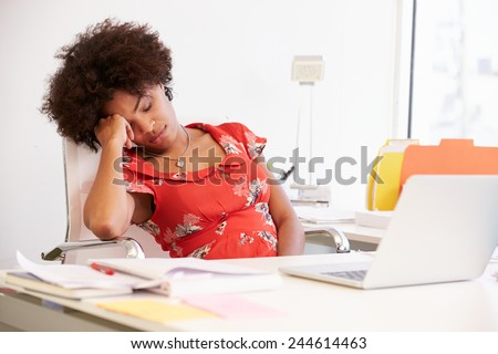 Tired Woman Working At Desk In Design Studio - stock photo