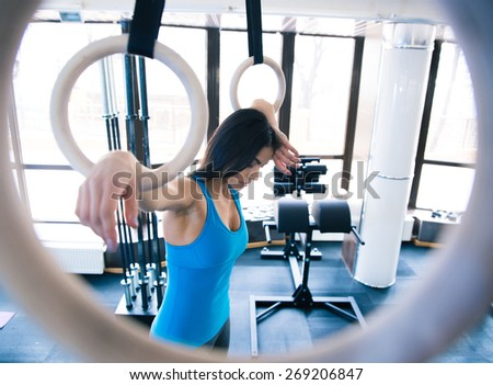 Tired woman working out on gimnastick rings at gym - stock photo