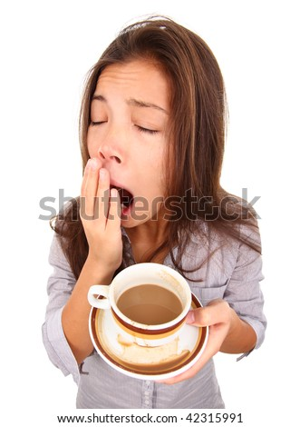 Tired woman yawning spilled a little coffee. Beautiful mixed race asian / caucasian model isolated on white background. - stock photo