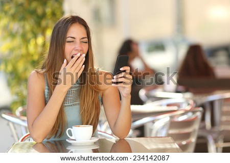 Tired woman yawning while is working on the phone at breakfast in a restaurant - stock photo