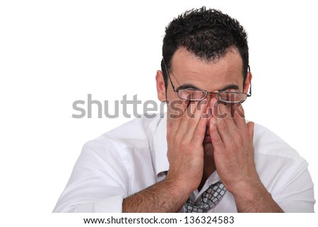 Tired worker rubbing his eyes - stock photo