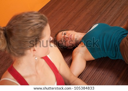 Tired Yoga practitioners rest on a mat during a workout - stock photo