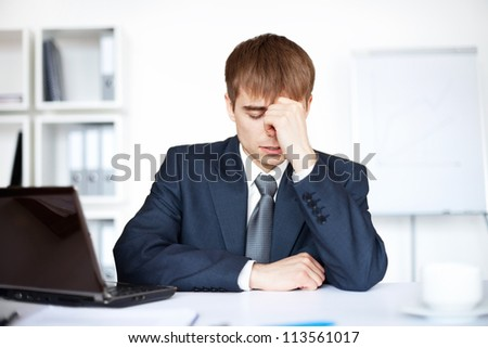 Tired young business man with problems and stress in bright office - stock photo