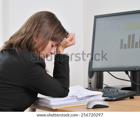 Tired young business woman in depression sitting at computer on workplace - stock photo
