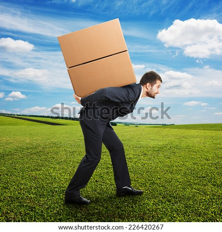 tired young businessman carrying two heavy boxes on the field - stock photo