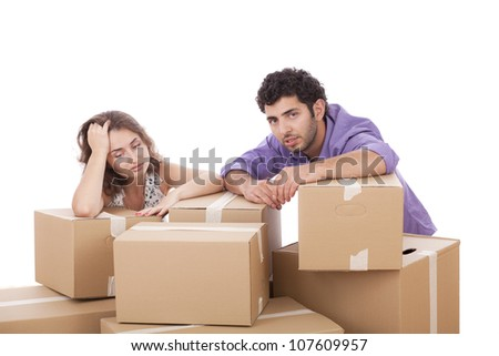 Tired young couple with cardboard boxes over white background - stock photo