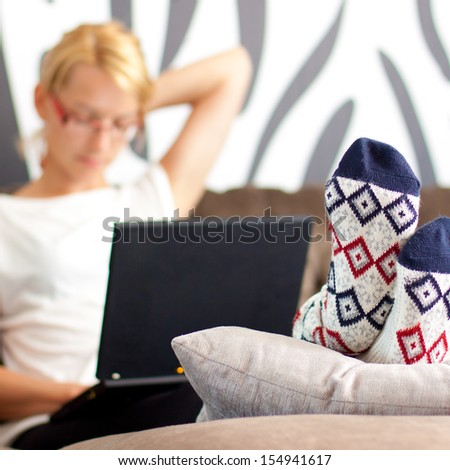 Tired young lady having pain in the neck from excessive laptop usage. - stock photo