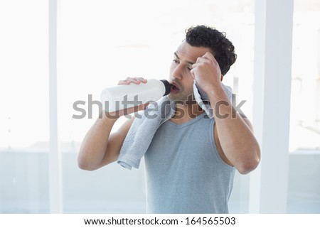 Tired young man drinking water while wiping sweat with towel in a bright fitness studio - stock photo