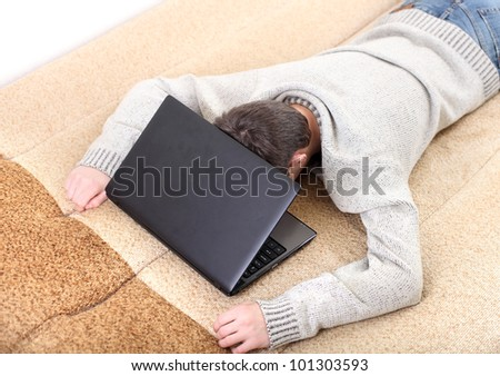tired young man falling asleep with notebook on sofa - stock photo